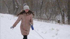 Het gelukkige meisje met hond speelt looppas en lacht in een blizzard Langzame Motie stock video