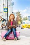 Het gelukkige meisje met stadskaart zit alleen op roze bagage Stock Fotografie