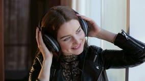 Het gelukkige meisje ontspannen die aan muziek met hoofdtelefoons luisteren stock videobeelden