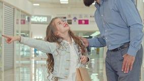 Het gelukkige meisje richten op jonge geitjes slaat op, winkelend bij de wandelgalerij met haar vader stock videobeelden