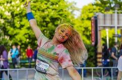 Het gelukkige meisje schilderde met gekleurd poeder Stock Foto