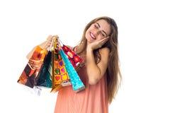 Het gelukkige meisje sloot haar ogen en houdt in zijn hand heel wat mooie die pakketten op witte achtergrond worden geïsoleerd Stock Afbeeldingen