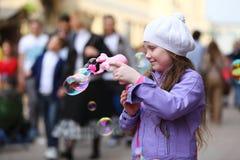 Het gelukkige meisje speelt met zeepbelskanon op de straat stock foto