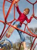 Het gelukkige meisje spelen bij speelplaats. Stock Fotografie