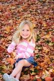 Het gelukkige meisje spelen in bladeren Stock Foto's