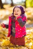 Het gelukkige meisje spelen in het de herfstpark Royalty-vrije Stock Afbeeldingen