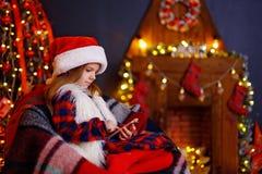 Het gelukkige meisje spelen met haar slimme telefoon door een open haard in een comfortabele donkere woonkamer op Kerstmisvooravo stock afbeelding