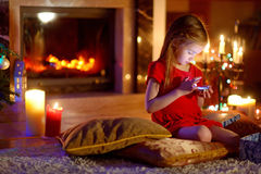 Het gelukkige meisje spelen met haar slimme telefoon op Kerstmisvooravond Royalty-vrije Stock Foto