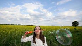 Het gelukkige meisje spelen onder zeepbels op groene weide in de zomer stock video