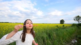 Het gelukkige meisje spelen onder zeepbels op groene weide in de zomer stock videobeelden