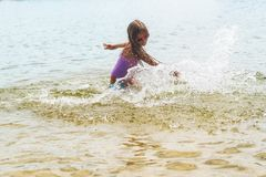 Het gelukkige meisje spelen in ondiep watergolven Gelukkig meisje royalty-vrije stock fotografie