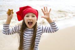 Het gelukkige meisje spelen op het strand Stock Foto's
