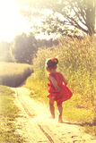 Het gelukkige meisje spelen op weide, zonsondergang, zomer Stock Foto