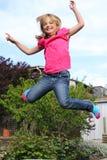Het gelukkige meisje springen Stock Afbeeldingen