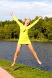Het gelukkige meisje springt op de bank van de rivier Stock Afbeelding