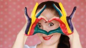 Het gelukkige meisje toont hart met behulp van handen dichte omhooggaand Hand vuile geschilderde kleurrijk Het concept geluk, lie stock videobeelden