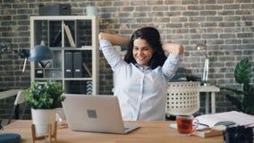 Het gelukkige meisje typen met laptop die dan het uitrekken zich wapens ontspannen die in bureau glimlachen stock video