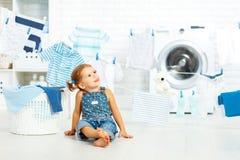 Het gelukkige meisje van de kindpret om kleren en lach in laund te wassen stock afbeeldingen