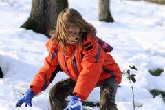 Het gelukkige meisje vechten met sneeuwballen Stock Foto