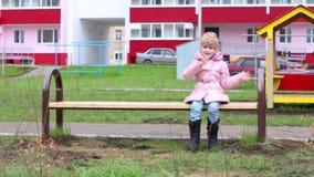 Het gelukkige meisje in warme kleren zit op bank stock footage