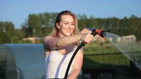 Het gelukkige meisje water geven met gieter stock footage