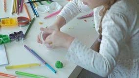 Het gelukkige meisje zet multicolored plasticine in een container, op de Desktop zijn cijfers en kleurpotloden, stock videobeelden