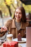 Het gelukkige meisje zit in een koffie, drinkend koffie met chocoladedessert Zij lepelt in een kop van koffie en lacht Stock Afbeeldingen