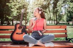 Het gelukkige meisje zit op bank met haar gekruiste benen en kijkt aan de kant Zij houdt cassete in linkerhand en stock fotografie