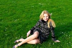 Het gelukkige meisje zit op een bloeiende de lenteweide Royalty-vrije Stock Fotografie