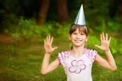 Het gelukkige meisjekind leuk en mooi in feestelijke kegelkappen, heeft pret verjaardag vieren royalty-vrije stock foto's