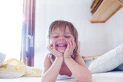 Het gelukkige meisjesdochter glimlachen en het maken zien het bekijken camera op ouder` s bed bij onder ogen ochtend Gelukkig ont Stock Afbeelding
