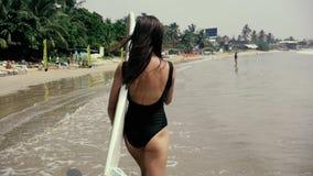 Het gelukkige meisjessurfer lopende vrolijk lachen hebbend pret met het surfen boogieboard op de zomervakantie stock footage