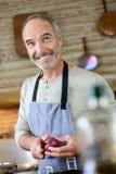 Het gelukkige mens koken in keuken Stock Foto