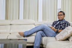 Het gelukkige mens spelen met tablet thuis stock fotografie
