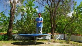 Het gelukkige mens springende spelen op trampoline stock footage