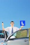 Het gelukkige mens stellen dichtbij zijn auto, houdend l-teken en sleutel op een weg Royalty-vrije Stock Afbeelding