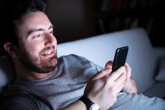 Het gelukkige mens texting op mobiele telefoon bij nacht stock afbeeldingen