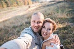Het gelukkige middenleeftijdspaar maakt in openlucht selfie stock foto