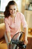 Het gelukkige moderne vrouw swtitching op metaalvloer bevindende ventilator royalty-vrije stock foto's