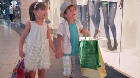 Het gelukkige modieus winkelen, weinig jongen en meisje met pakketten in handen na aankopen gaat voorbij winkelvensters tijdens z stock videobeelden