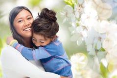Het gelukkige moeder en dochter koesteren stock afbeeldingen