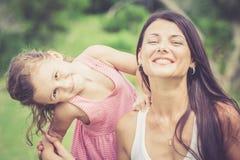 Het gelukkige moeder en dochter spelen in het park in de dagtijd Stock Afbeeldingen