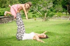 Het gelukkige moeder en dochter spelen in het park in de dagtijd Royalty-vrije Stock Afbeeldingen