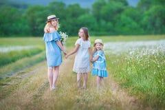 Het gelukkige moeder en dochterkind samen met gele paardebloembloemen in de zomerdag geniet samen gelukkige vakantie van vrije ti royalty-vrije stock foto