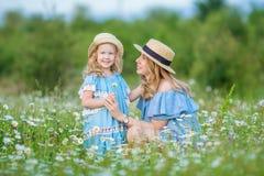 Het gelukkige moeder en dochterkind samen met gele paardebloembloemen in de zomerdag geniet samen gelukkige vakantie van vrije ti royalty-vrije stock afbeeldingen