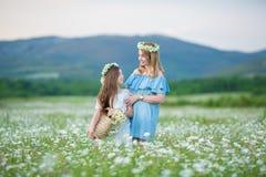 Het gelukkige moeder en dochterkind samen met gele paardebloembloemen in de zomerdag geniet samen gelukkige vakantie van vrije ti royalty-vrije stock fotografie