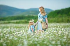 Het gelukkige moeder en dochterkind samen met gele paardebloembloemen in de zomerdag geniet samen gelukkige vakantie van vrije ti stock foto