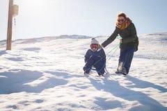 Het gelukkige moeder en kind spelen in de sneeuw met een slee Stock Afbeeldingen