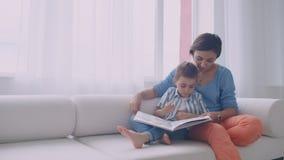 Het gelukkige moeder en kindboek die van de zoonslezing in bed lachen Gelukkig van het familiemoeder en kind de holdingsboek die  stock videobeelden