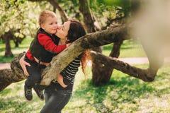 Het gelukkige moeder en peuterzoon openlucht spelen samen en het beklimmen van appelboom stock foto's